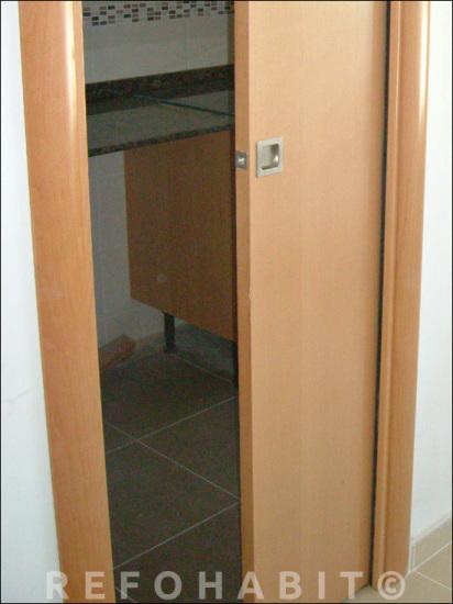 Porta corredissa col·locada a cuina, amb tirador quadrat